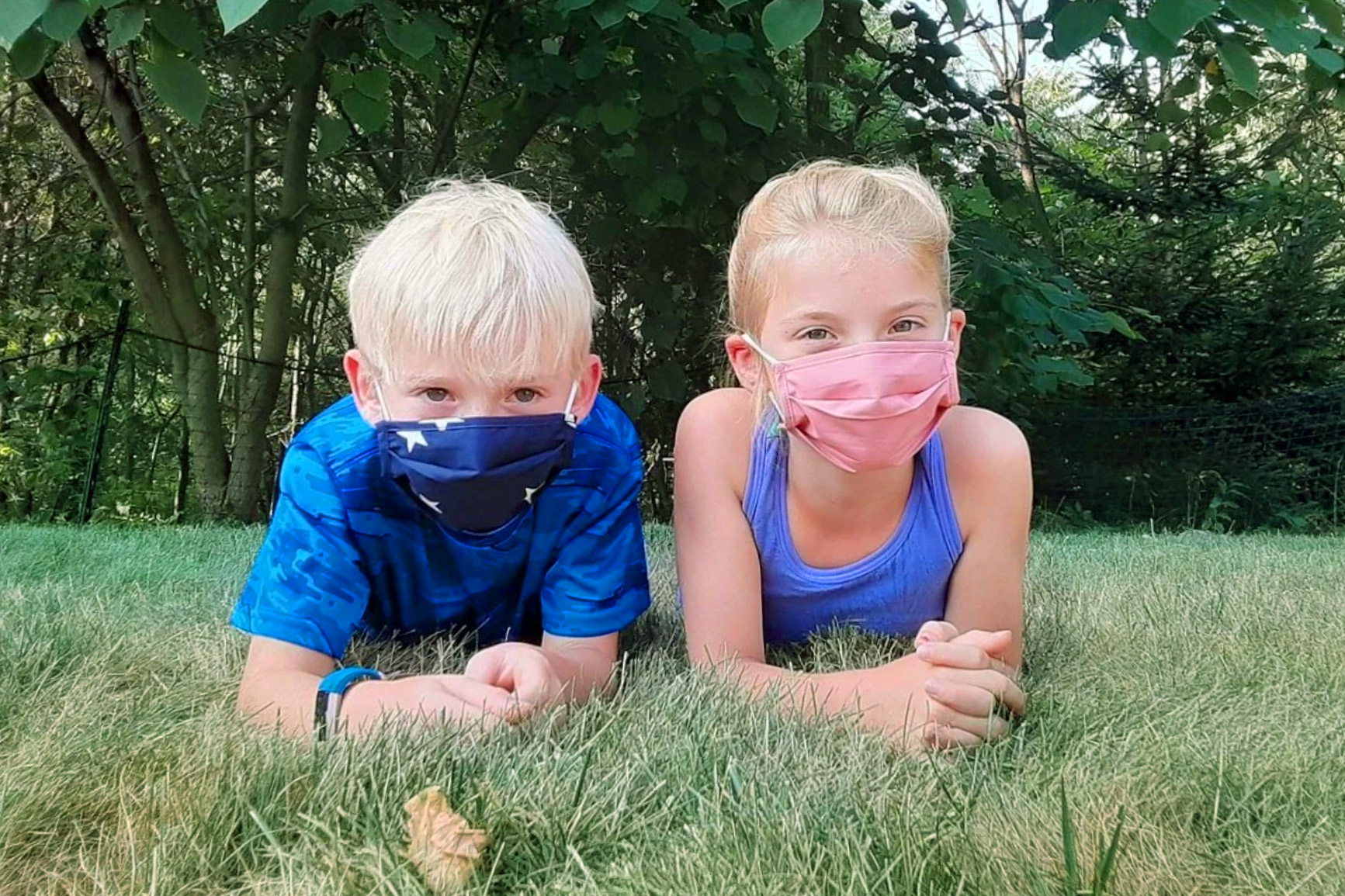 Kids with masks in grass